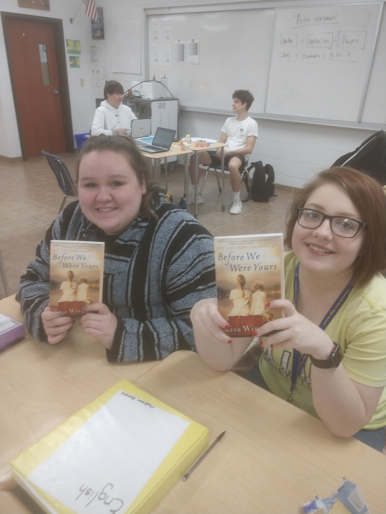 Students showing off one of the books.